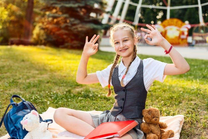 Uczennicy ono uśmiecha się i pokazuje radosny ok znak uczeń siedzi w parku na koc z miękkiej części zabawki zabawkami niedźwiedź  fotografia royalty free