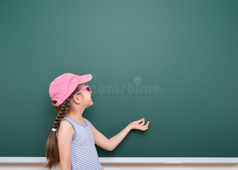 Uczennicy sztuka blisko blackboard Chwyty coś w ona ręki Opróżnia przestrzeń jest edukacja starego odizolowane pojęcia zdjęcia royalty free