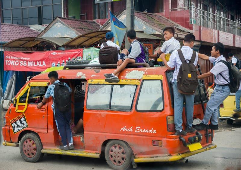 Uczni wieki dojrzewania iść inside i outside na czerwonym samochodzie dostawczym szkolny Singapur zdjęcie stock