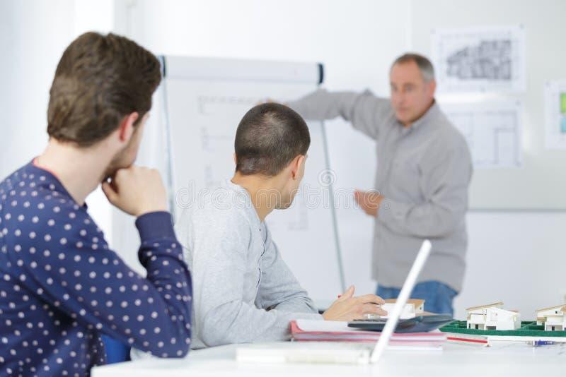 2 ucznia słucha nauczyciel w sala lekcyjnej z notatnikiem obrazy royalty free