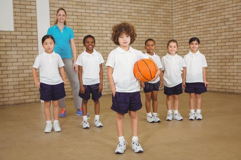 Ucznie bawić się koszykówkę wpólnie wokoło obrazy royalty free