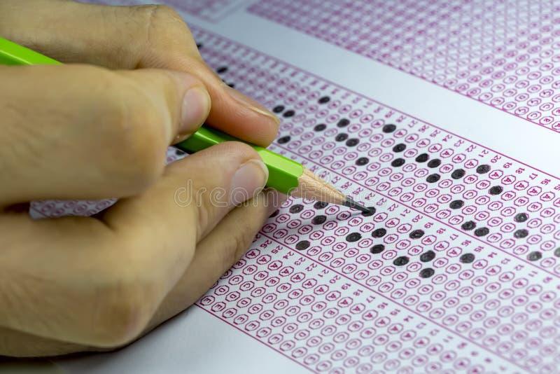 Ucznie bierze egzaminy, pisze egzaminacyjnym pokoju z mienie ołówkiem na okulistycznej formie znormalizowany test z odpowiedziami zdjęcia stock