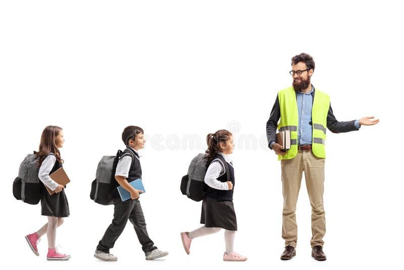 Ucznie chodzi w linii i nauczycielu z gestykuluje cześć zdjęcia stock