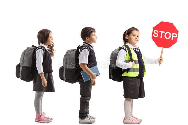 Ucznie czeka w linii z jeden one jest ubranym bezpieczeństwo fotografia stock