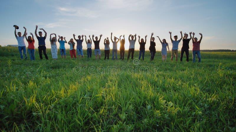 Ucznie mówją szkoła do widzenia Ucznie macha ich ręki przeciw tłu położenia słońce fotografia royalty free