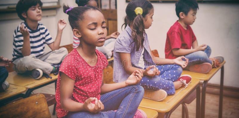 Ucznie medytuje w lotosowej pozyci na biurku w sala lekcyjnej fotografia royalty free