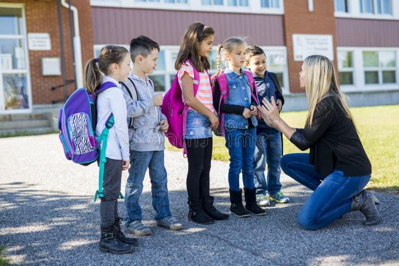 Ucznie na zewnątrz nauczyciela stoi wpólnie fotografia royalty free