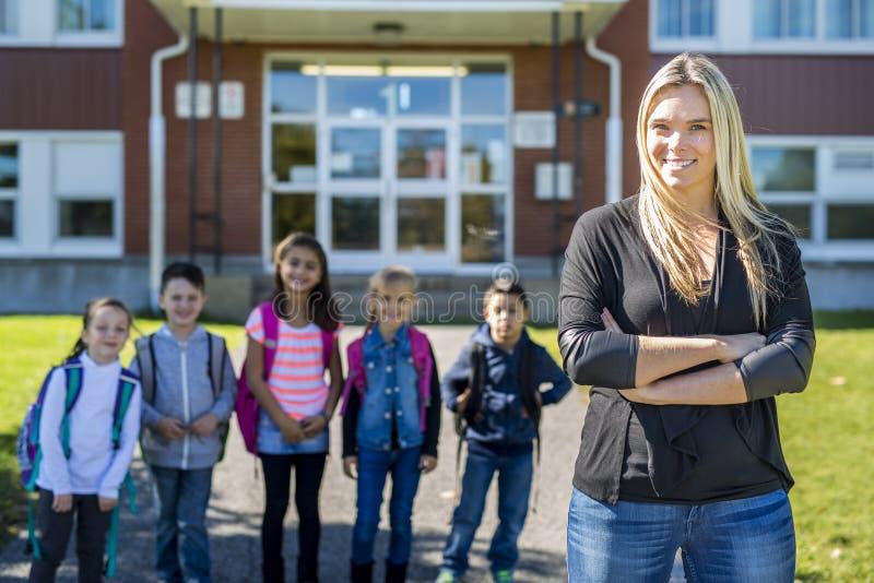 Ucznie na zewnątrz nauczyciela stoi wpólnie zdjęcie stock