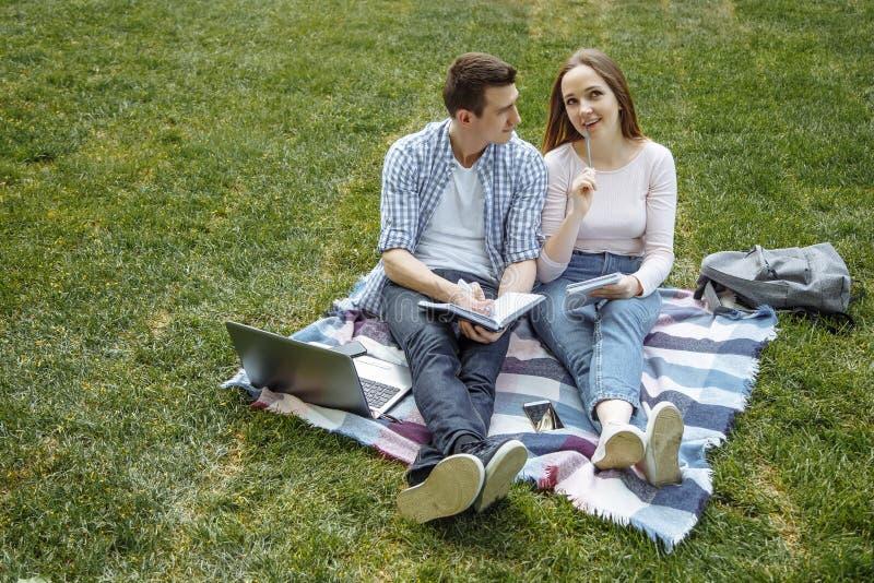 Ucznie ono uśmiecha się podczas gdy czytający laptop na zielonej trawie i używać w parku edukacja szczęśliwa zdjęcia royalty free