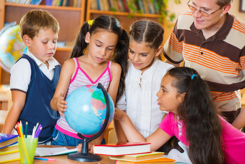Ucznie patrzeje kulę ziemską z ich nauczycielem zdjęcia stock