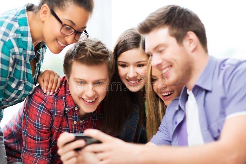 Ucznie patrzeje smartphone przy szkołą zdjęcia royalty free