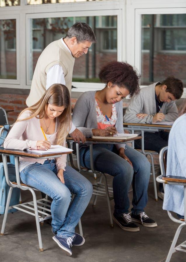 Ucznie Pisze egzaminie Podczas gdy profesora Doglądać fotografia stock