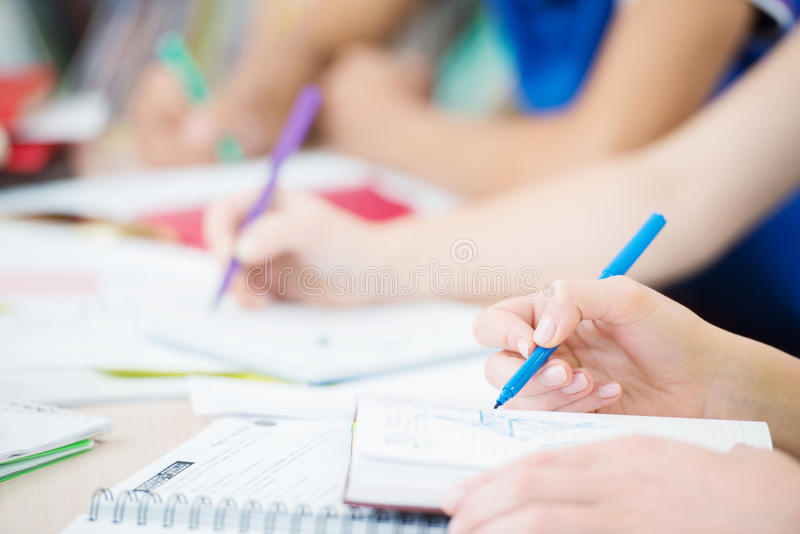 Ucznie pisze w sala lekcyjnej, zamykają up zdjęcia stock