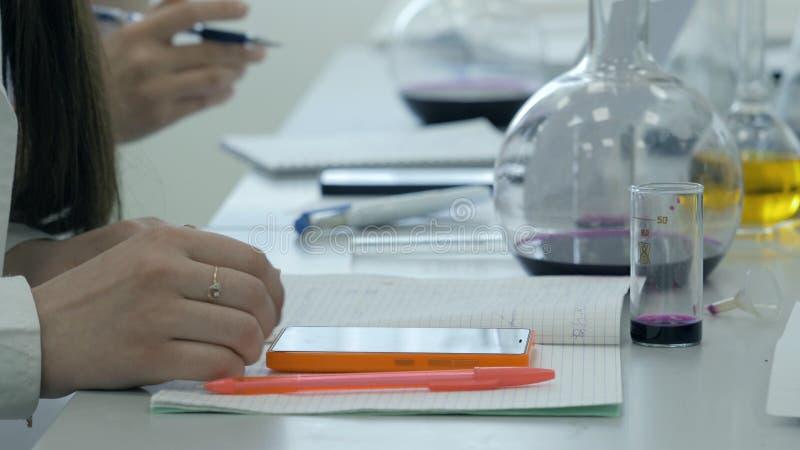 Ucznie przy pracą w laboratorium chemia biorą notatki w notatniku Żeński uczeń Używa telefon W nauki lekci zdjęcia royalty free