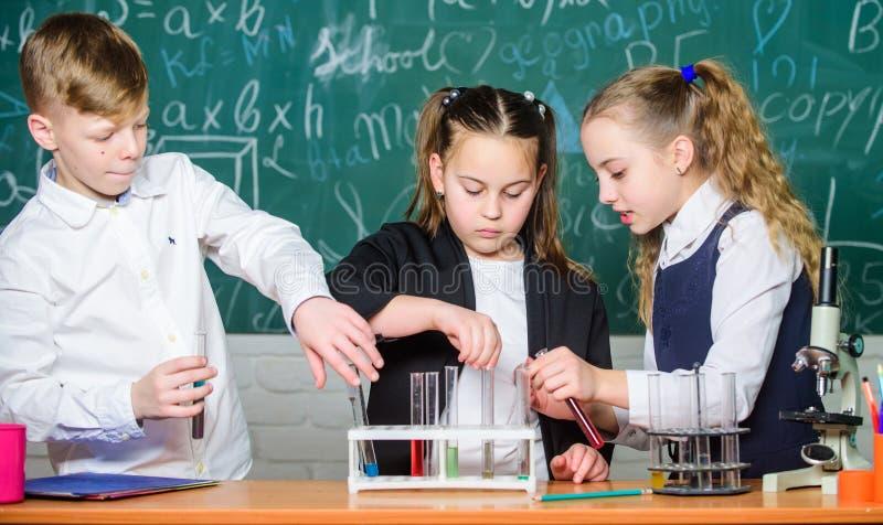 ucznie robi biologii eksperymentuj? z mikroskopem w lab Ma?e dzieci uczy si? chemi? Patrzeć przyszłość obrazy royalty free