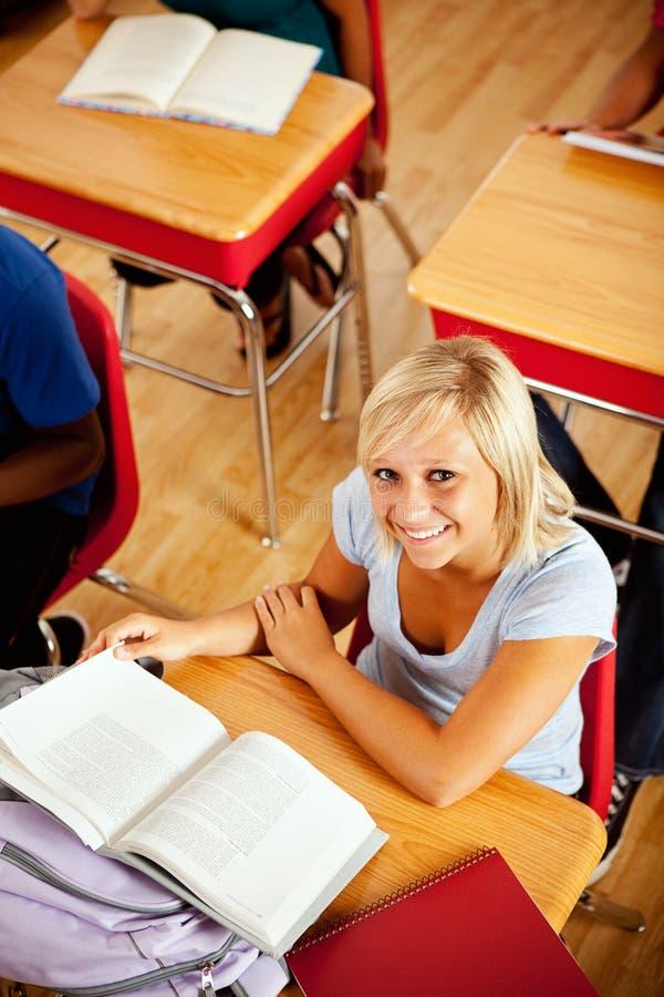 Ucznie: Rozochocony Żeński uczeń Pracuje Przy biurkiem zdjęcie stock