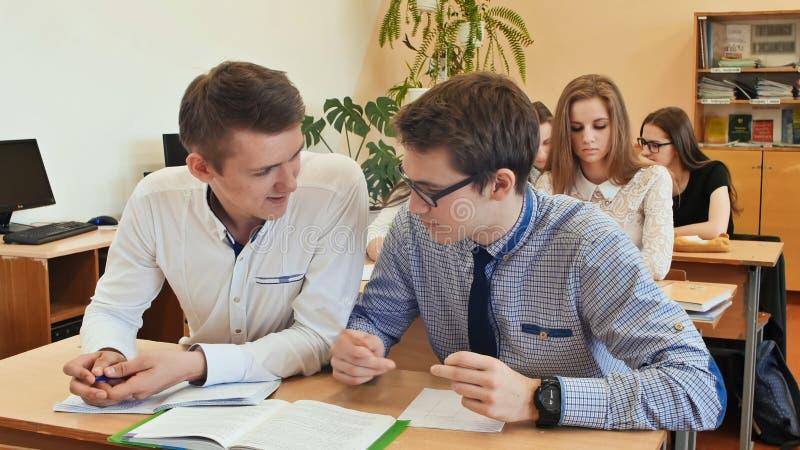 Ucznie studiują w sala lekcyjnej przy szkolnym biurkiem zdjęcie stock