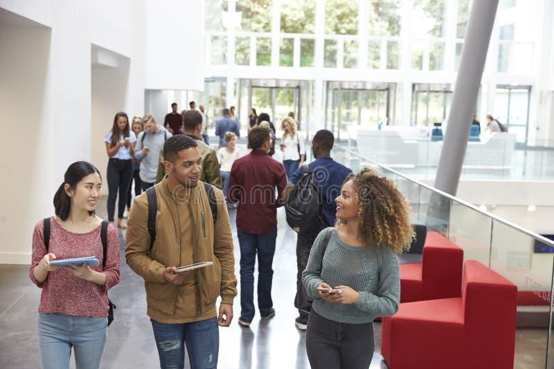 Ucznie trzyma pastylki i telefon rozmowę w uniwersytecie lobbują obrazy stock