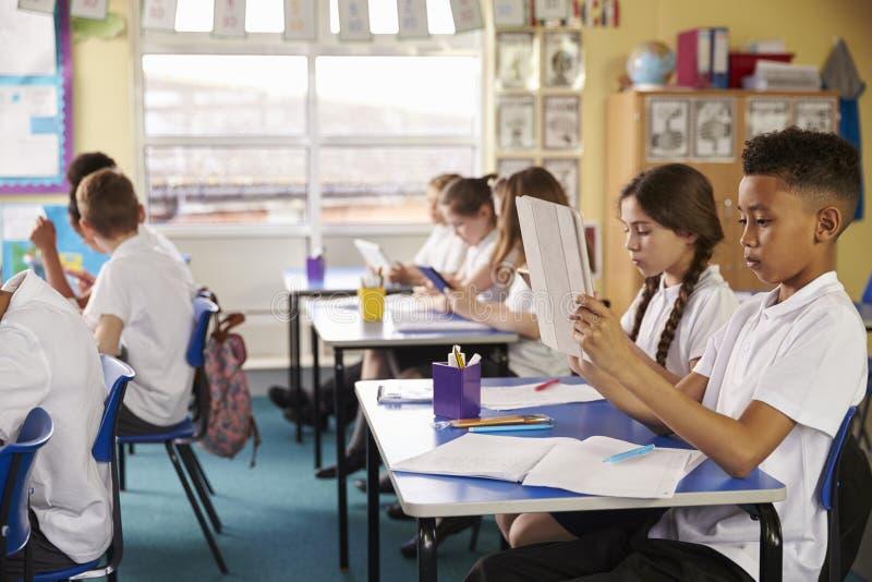 Ucznie używa pastylka komputery w klasie przy szkołą podstawową obraz royalty free
