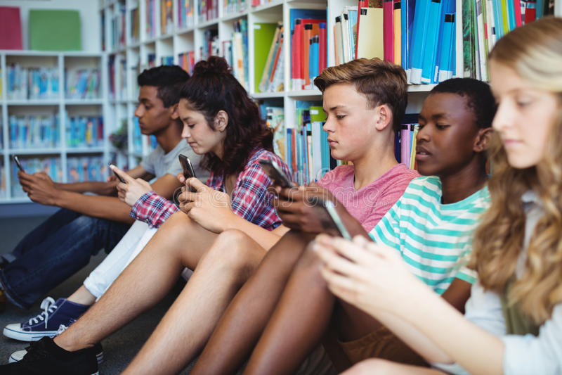 Ucznie używa telefon komórkowego w bibliotece zdjęcia royalty free