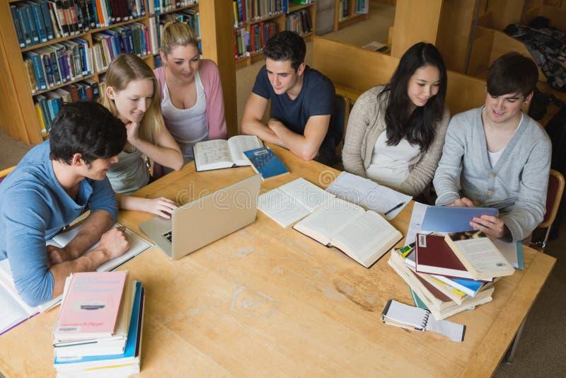 Ucznie uczy się z laptopem i pastylką w bibliotece zdjęcia stock