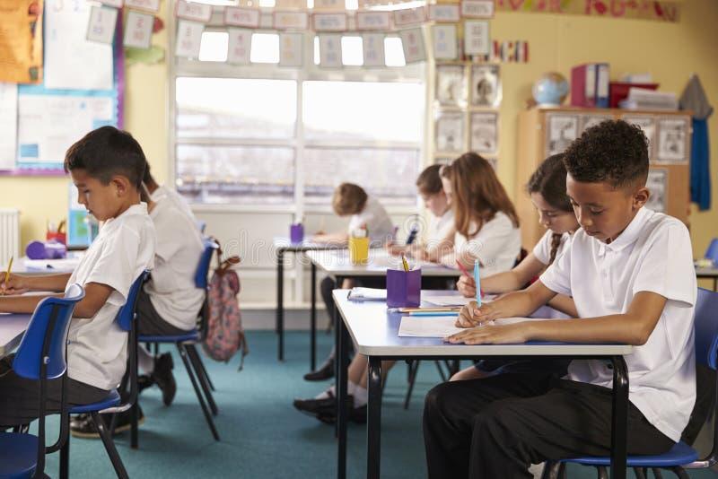 Ucznie w lekci przy szkoły podstawowej sala lekcyjną, boczny widok zdjęcie stock