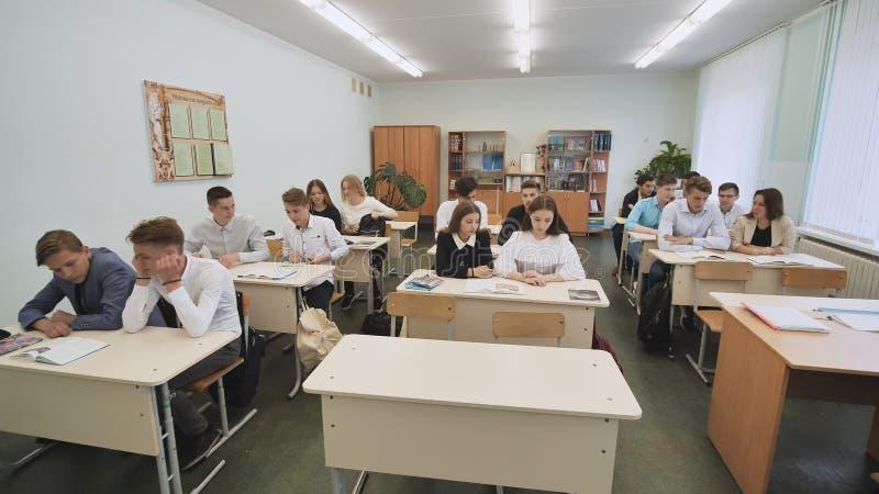 Ucznie w sala lekcyjnej siedzą przy szkolnymi biurkami przed lekcją Rosjanin szkoła obrazy stock