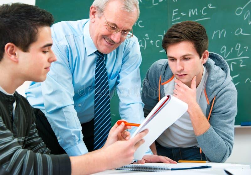 Ucznie z nauczycielem w sala lekcyjnej zdjęcia stock