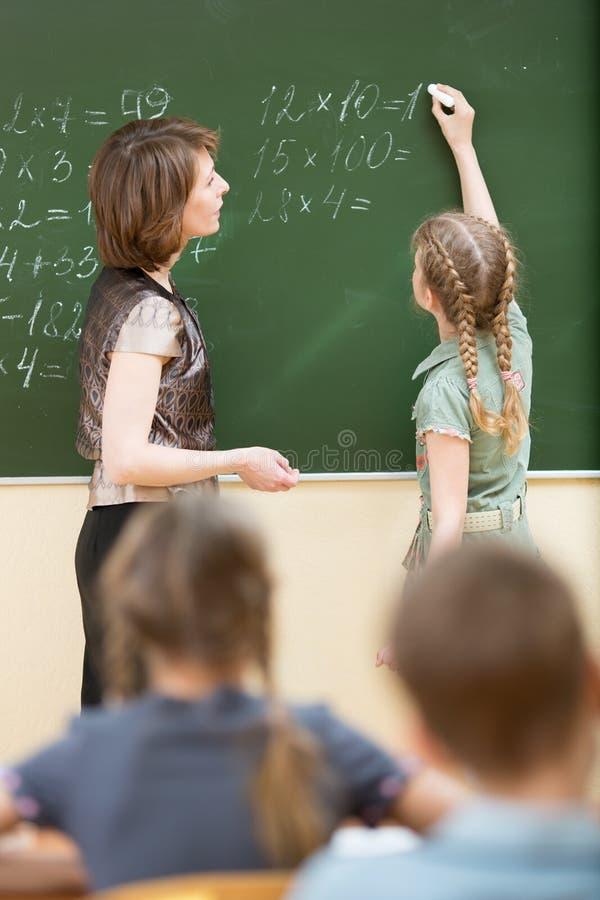 Ucznie z nauczycielem w sala lekcyjnej Uczeń rozwiązuje zadanie i pisze na blackboard obrazy royalty free