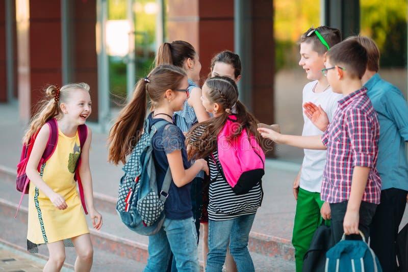 Uczniowie chodzą do szkoły. Uczniowie witam się nawzajem obrazy stock