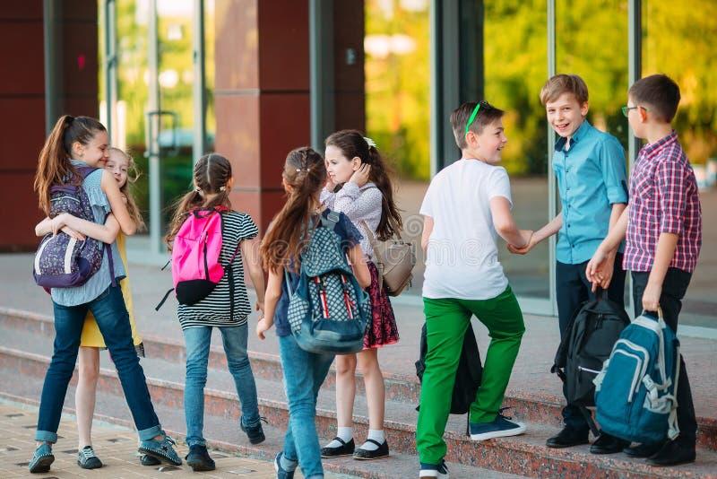 Uczniowie chodzą do szkoły. Uczniowie witam się nawzajem obraz stock