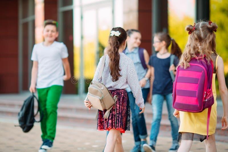 Uczniowie chodzÄ… do szkoÅ'y. Uczniowie witam siÄ™ nawzajem zdjęcia stock