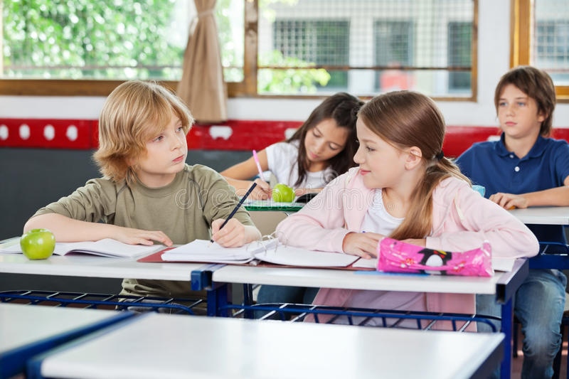 Uczniowska Patrzeje dziewczyna Podczas gdy Pisać Przy biurkiem obrazy stock
