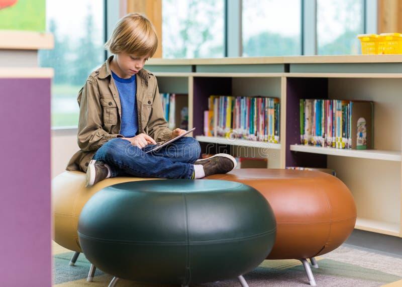 Uczniowska Używa Cyfrowej pastylka W bibliotece obraz royalty free