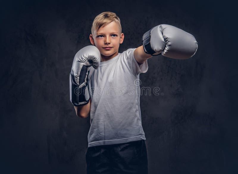 Uczniowski bokser jest ubranym bokserskich rękawiczek przedstawienia z blondynka włosy ubierał w białej koszulce bokserski kopnię obrazy stock