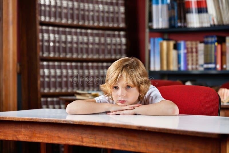 Uczniowski Patrzeć Oddalony Podczas gdy Opierający Na stole obrazy stock