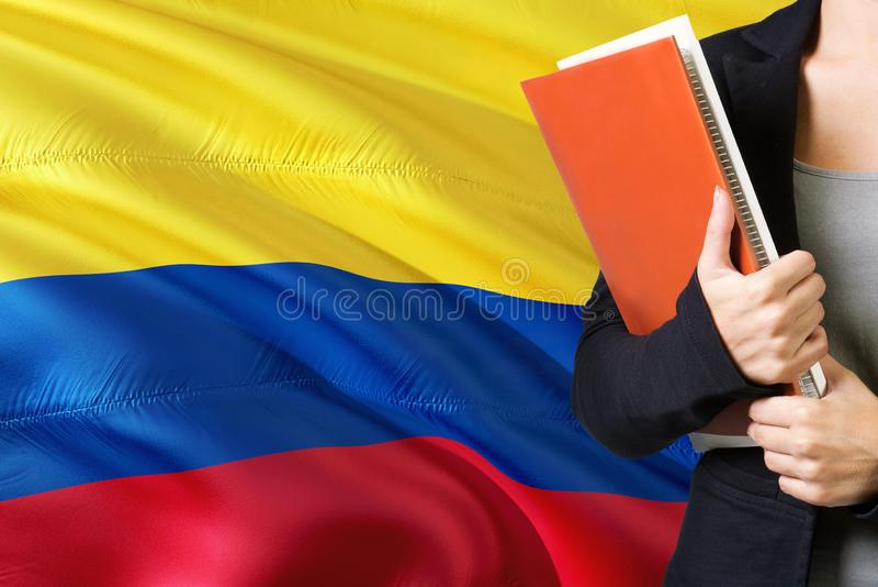 Uczyć się Kolumbijskiego językowego pojęcie Młodej kobiety pozycja z Kolumbia flagą w tle Nauczyciela mienia książki, pomarańcze fotografia stock
