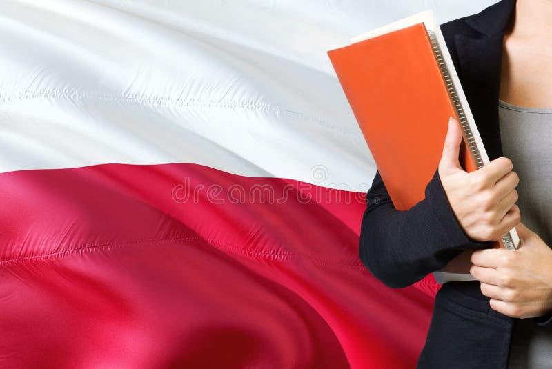 Uczyć się Polskiego językowego pojęcie Młodej kobiety pozycja z Polska flagą w tle Nauczyciela mienia ksi??ki, pomara?czowy puste fotografia stock