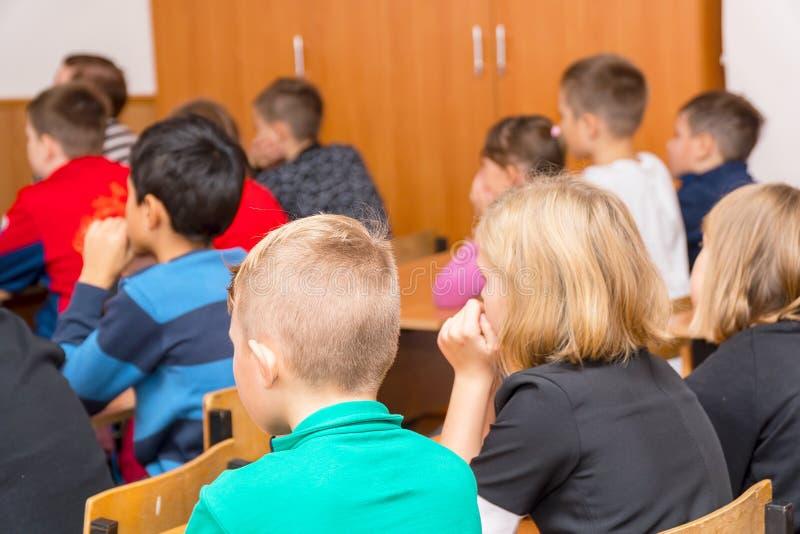 Uczy kogoś dzieciaków w sali lekcyjnej obsiadaniu przy ich biurkami i słucha nauczyciel zdjęcia royalty free