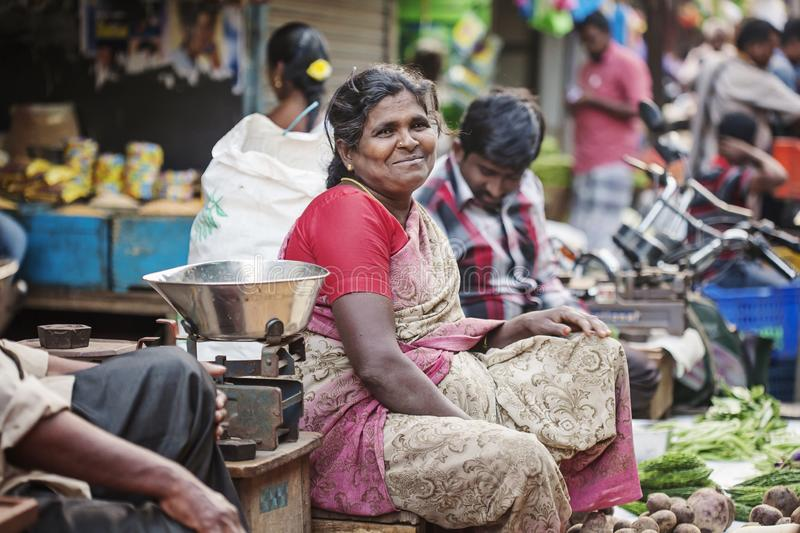 Indian vegetable outdoor street market female seller. Udaipur city in Rajasthan, India, January 2018: Indian vegetable outdoor street market female seller stock image