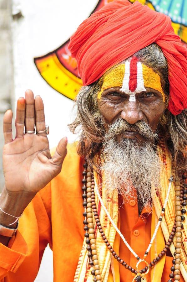 Udaipur, India, Wrzesień 14, 2010: Święty mężczyzna w oragne odzieżowym mieniu jego wręcza up obrazy royalty free