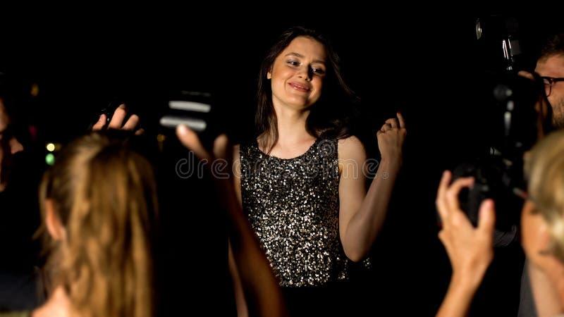 Udana aktorka w wspaniałej sukni wieczorowej, prezentująca kamery paparazzi, wydarzenie zdjęcia royalty free