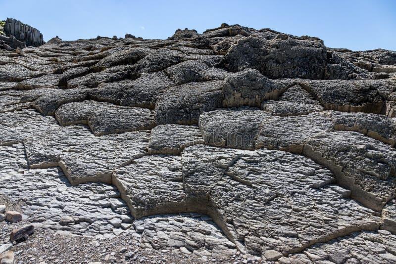 Udde Stolbchaty Udde på västkusten av ön av Kunashir Det komponeras av lager av basaltiska lavor av Mendeleyeven arkivfoto