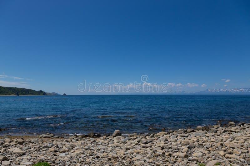 Udde Stolbchaty Udde på västkusten av ön av Kunashir Det komponeras av lager av basaltiska lavor av Mendeleyeven royaltyfria bilder