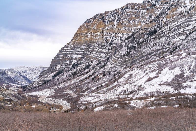 Uderzająca góra z brukującym drogowym cewieniem przez swój śnieżnego skłonu obrazy stock