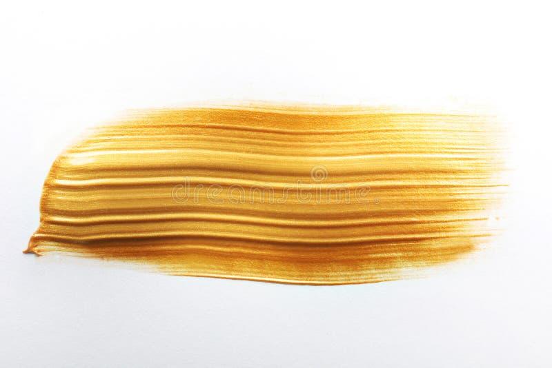 Uderzenie odizolowywający na bielu złocista farba zdjęcie stock