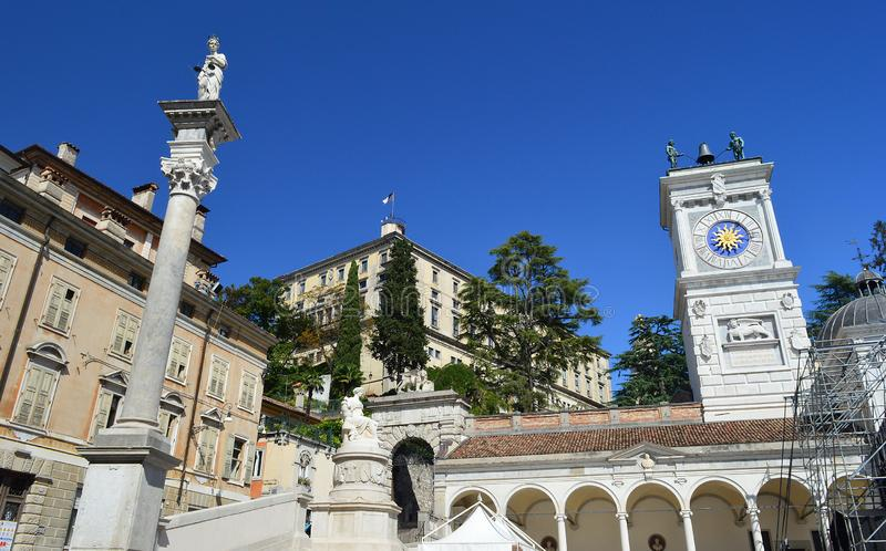 View from Piazza della Liberta, Udine, Italy. Udine Castle, Loggia di San Giovanni, Clock tower with 2 moorish figures striking the hour plus column statue of stock photos