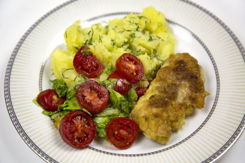 Udo smażył kurczak grul pomidory na talerzu odizolowywającym na białym tle obrazy royalty free