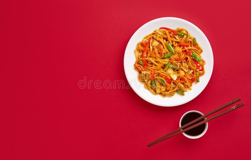 Udon beweegt gebraden gerechtnoedels met groenten Het Aziatische veganist vegetarische voedsel over rode vlakke achtergrond, legt stock afbeeldingen