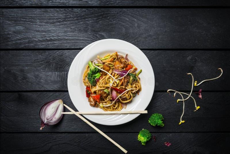 Udon beweegt gebraden gerechtnoedels met vlees of kip en groenten in een witte plaat met eetstokjes royalty-vrije stock fotografie